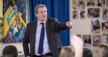 Damian Hinds pointing with his finger in a room of children
