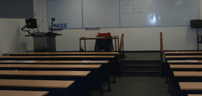 A room with rows of empty seats and a set of steps leading up to a platform with a whiteboard, a podium, and a microphone