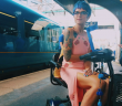 Sara Harvey in a pink dress on her scooter on a train platform