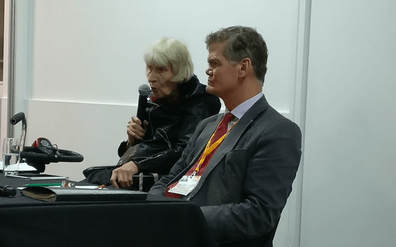Stephen Lloyd sitting next to Baroness Thomas who is speaking into a microphone
