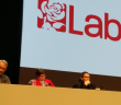 Three people sit behind a long desk on a stage on front of a giant Labour logo