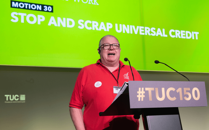 Dave Allan speaking in front of a screen saying stop and scrap universal credit
