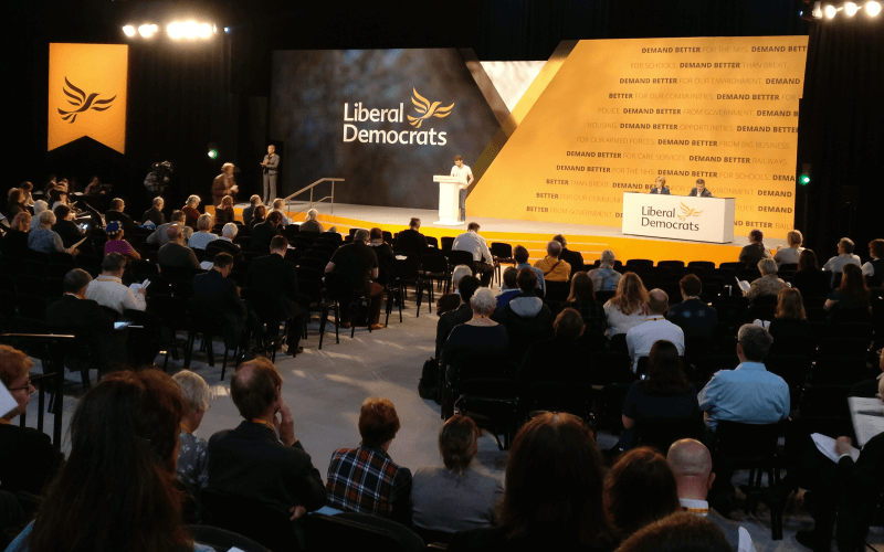 Conference delegates watch Henry Jones make a speech from the stage