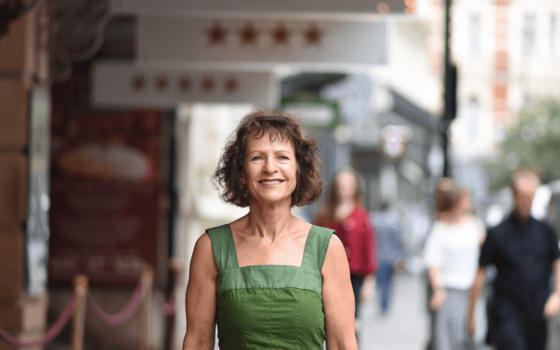 Jean St Clair, smiling, in a green dress in a street
