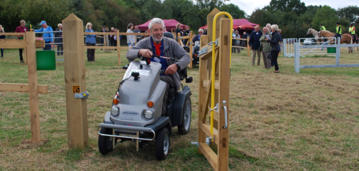 A man on an off-road scooter manoeuvres through an open gate