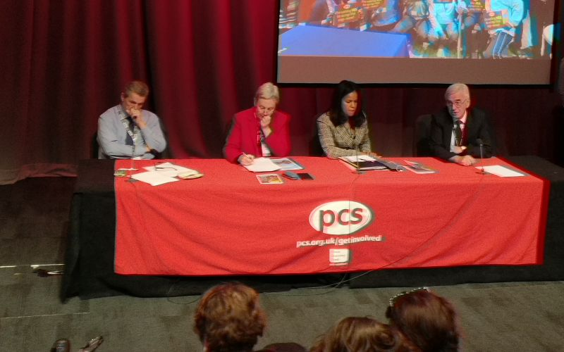 Four people, two men and two women, sit behind a long desk covered by a red cloth, with a PCS logo on the front