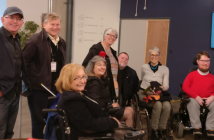 Eight people, including four wheelchair-users smiling at the camera