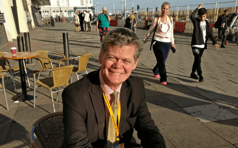 Stephen Lloyd sitting at a table watched by passers-by