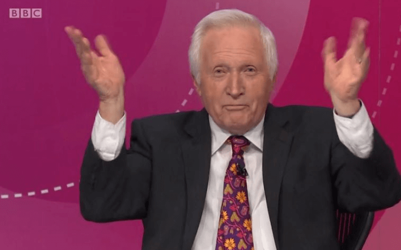 David Dimbleby waving his hands and smirking