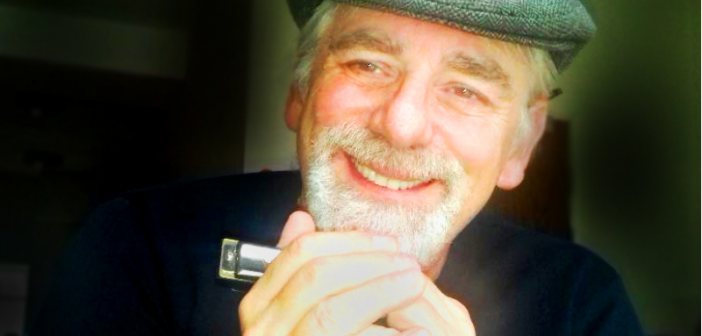 A smiling man in a flat cap holding a harmonica