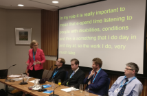 Sarah Newton standing and speaking, alongside four men sitting down, with words behind her on the screen about listening to disabled people