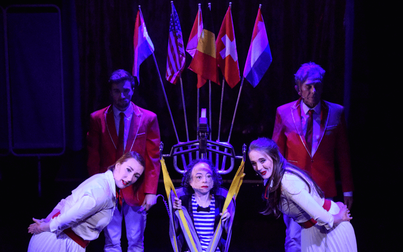 Liz Carr sits in a sling surrounded by two men and two woman, with various international flags above them