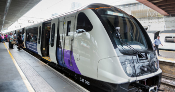 A white and purple train and carriages stationary at a platform