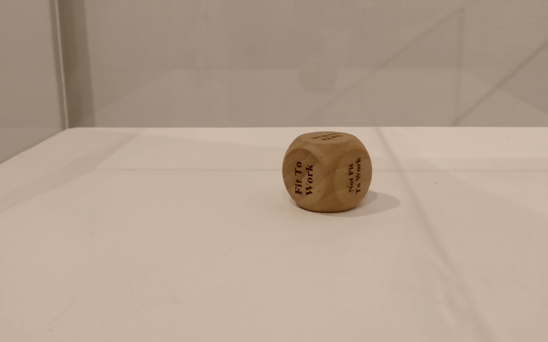 a wooden dice, with the words fit for work and not fit for work written on each of its sides, in a display case