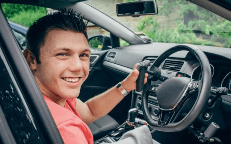 A disabled person sat in the riving seat of a car, smiling