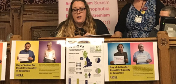 A woman speaks from a platform with campaigning pictures pinned to the table she is sitting at