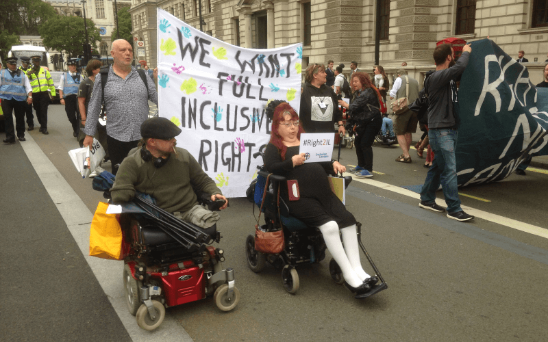 Andy Greene and Penny Pepper in electric wheelchairs at the head of a march in front of a banner calling for full inclusive rights