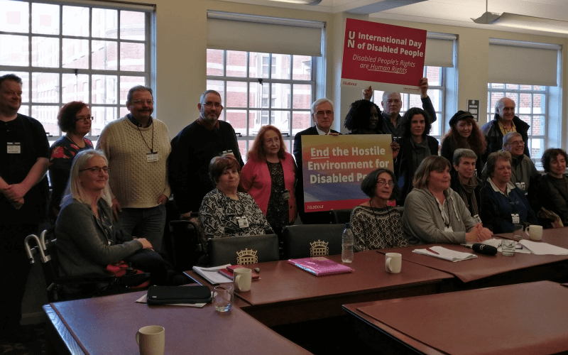 About 20 people, including John McDonnell, sitting and standin g in a room behind some tables and holding placards