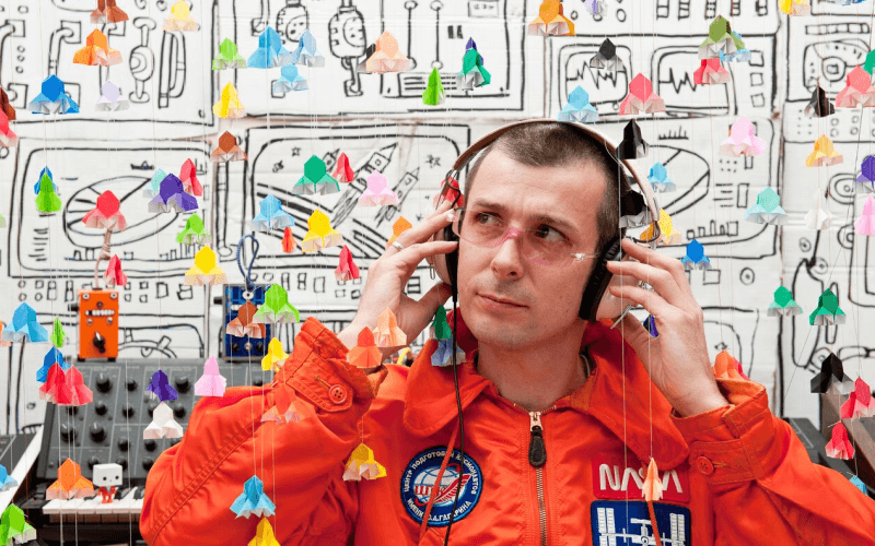 Rob Maddison in headphones and orange jumpsuit in front of a wall covered in cartoon illustrations