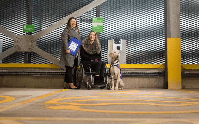 Two women, one in a wheelchair, next to an assistance dog in front of an electric vehicle charging point, with a wheelchair symbol in yellow on the ground in front