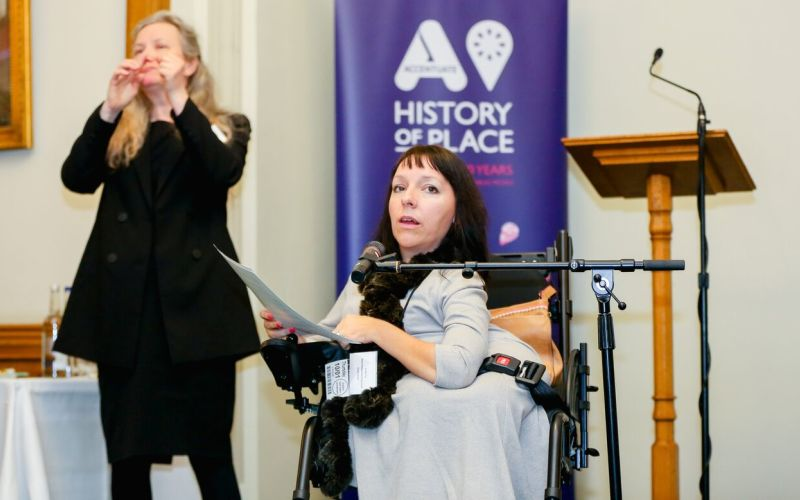 Esther Fox in her wheelchair in front of a sign saying History of Place, with a BSL interpreter beside her
