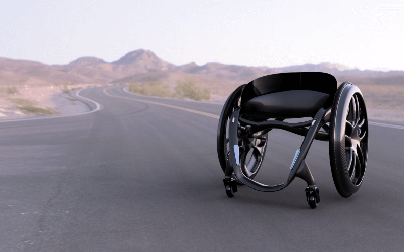 a black wheelchair in the middle of a road through a desert