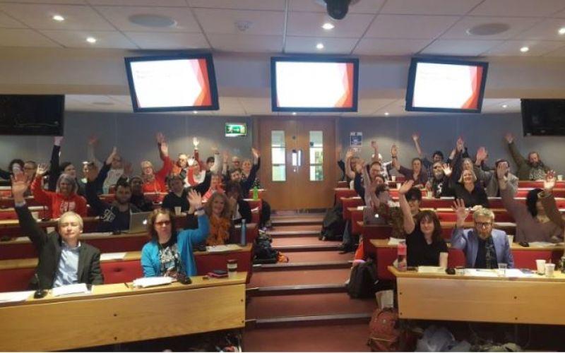 Lots of people in a seminar room raising their hands