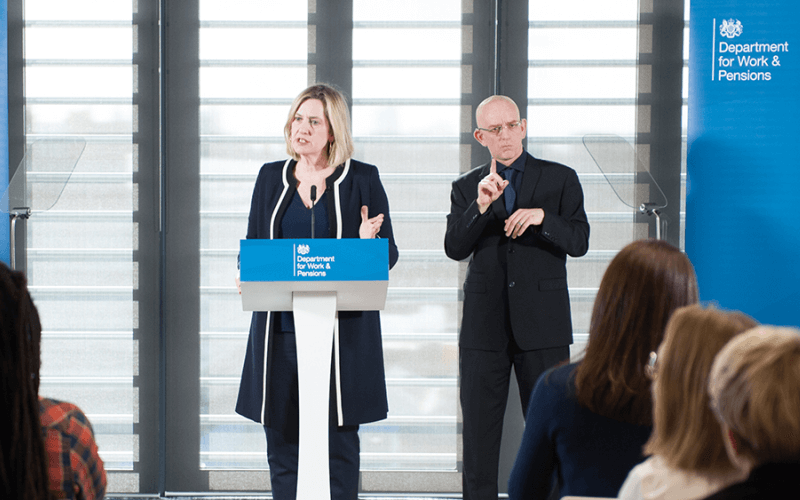 Amber Rudd at a lectern with a signer behind her