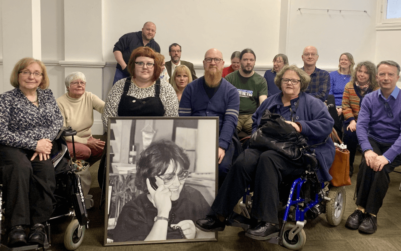 A group of people behind a large photo of Lorraine Gradwell