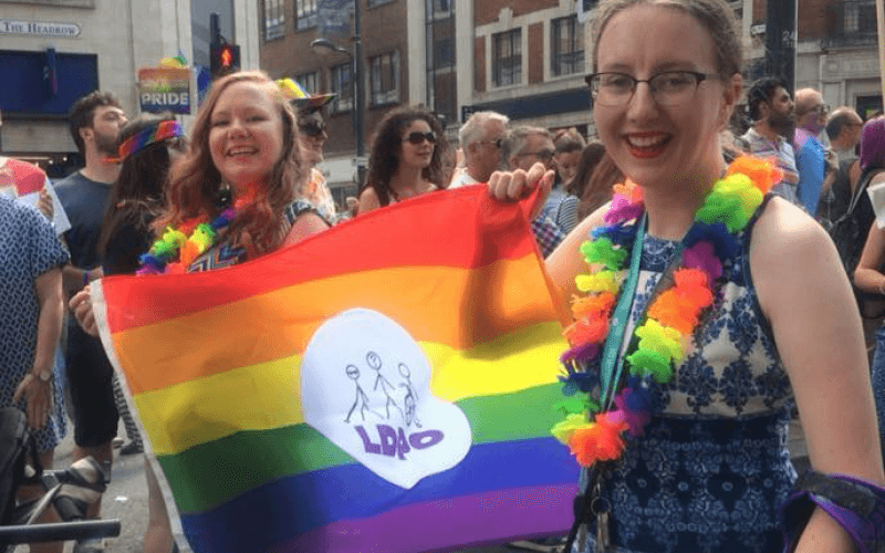 Two women holding a Leeds DPO rainbow flag
