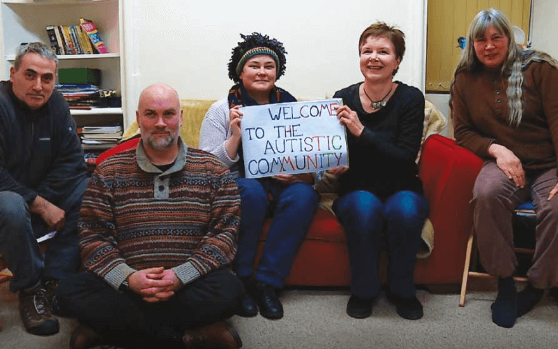 Five people hold a sign saying welcome to the autistic community