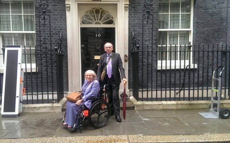 A female wheelchair-user and a man outside No 10