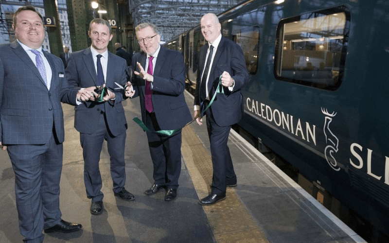 Four men in suits beside a train