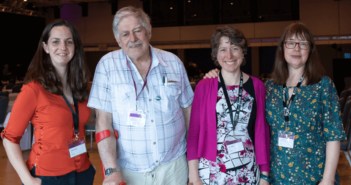 Four people in front of an empty conference hall