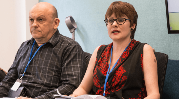 A woman, talking, sits next to a man