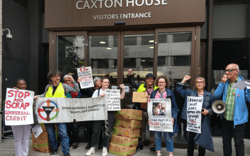 Activists with boxes of Metros outside DWP