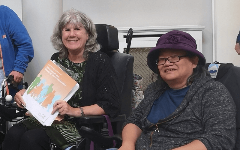 Two women, both wheelchair-users, one of them holding a document