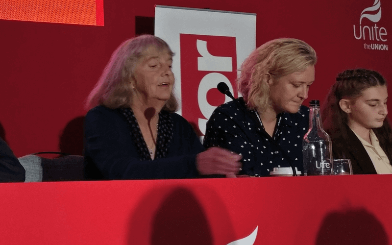 Two women behind a red table, with microphones