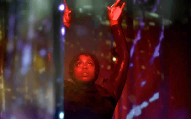 A woman raises her hands, with red and blue lights