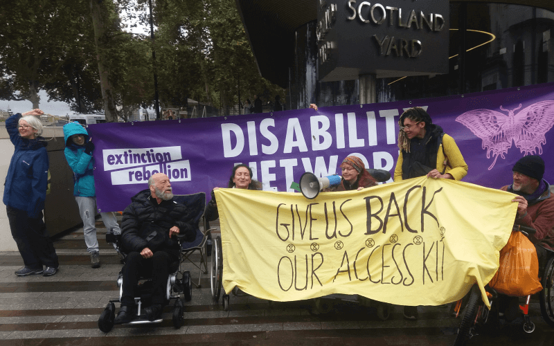 Four people holding a banner saying Give us back our access kit