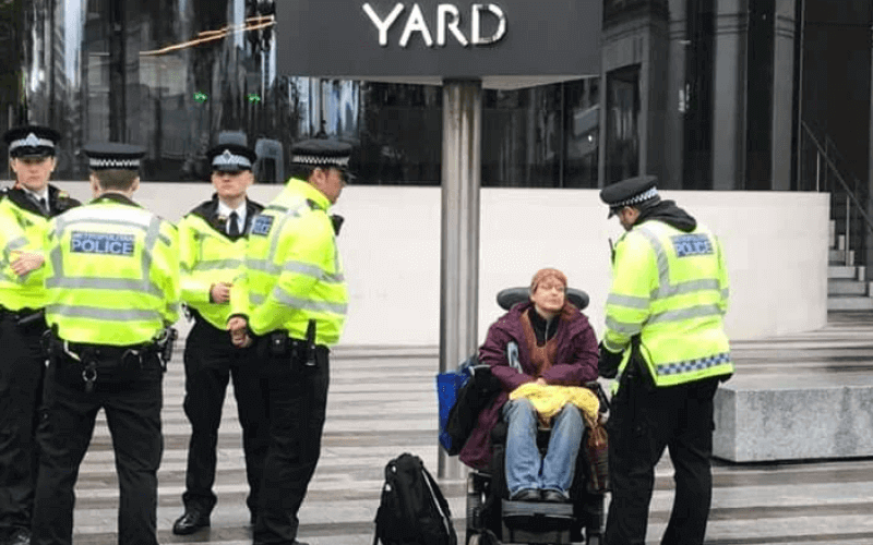 Nicki Myers in a wheelchair surrounded by police