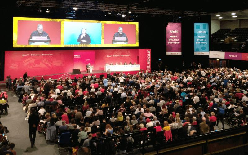 Hundreds of people listen to a speech