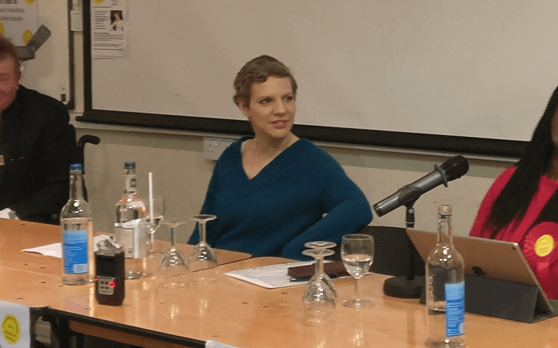Francesca Martinez behind a table and microphone