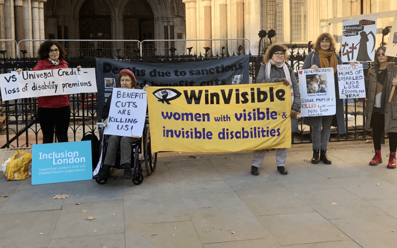 Women holding banners outside the Royal Courts of Justice