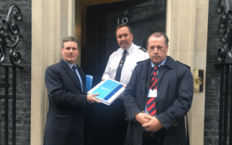 Two men and a police officer at the door to No 10