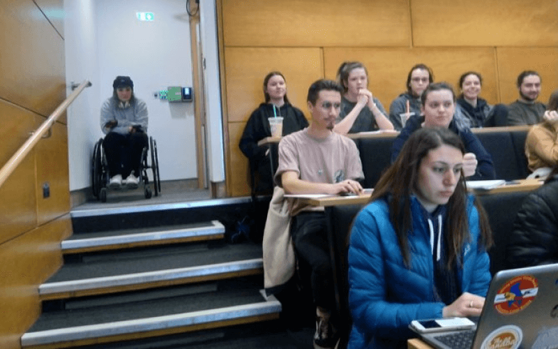 A wheelchair-user at the top of steps in a lecture theatre