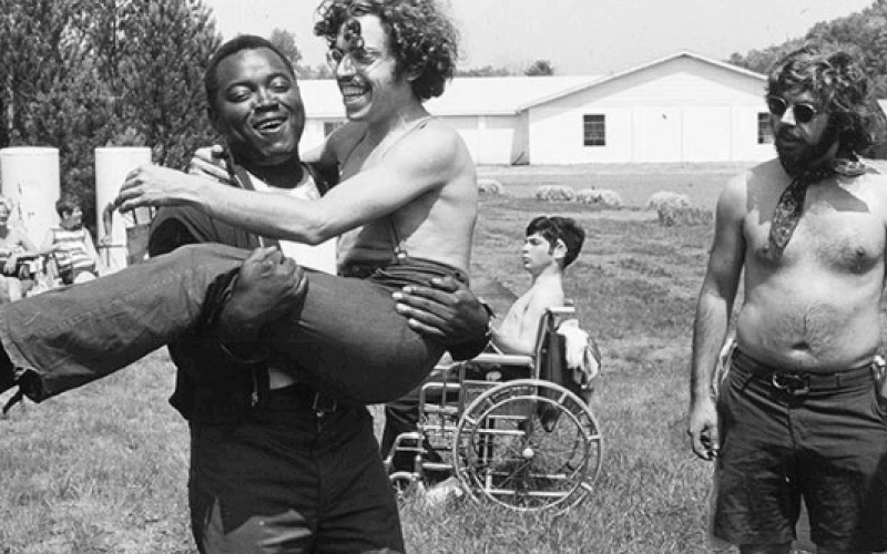 Black and white photo of disabled people in a field in the sun