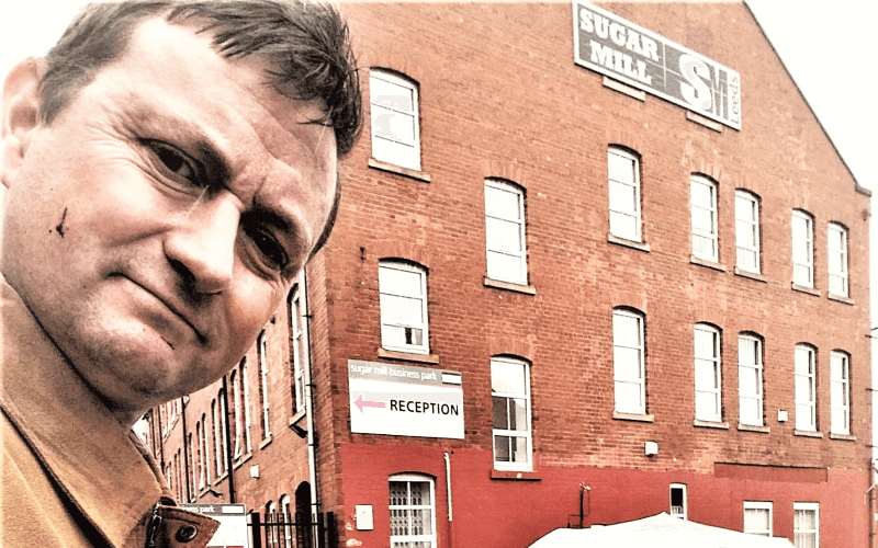A man outside a large red brick building