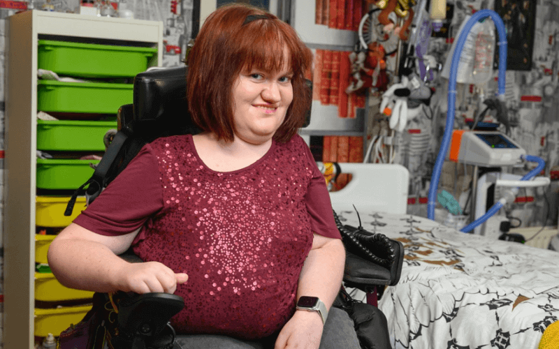 A woman sits in her bedroom in her powerchair