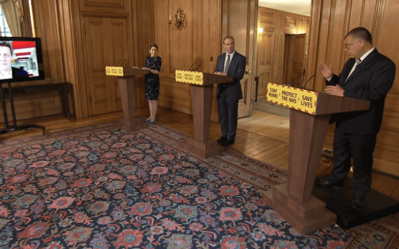 A woman and two men stand behind podiums